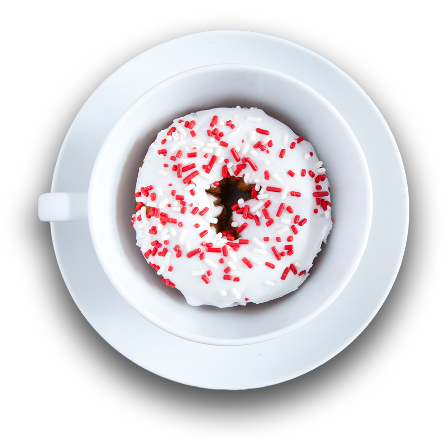 White coffee cup on saucer filled with a sprinkled donut